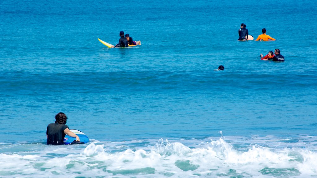 Legian Beach showing surfing and surf as well as a large group of people