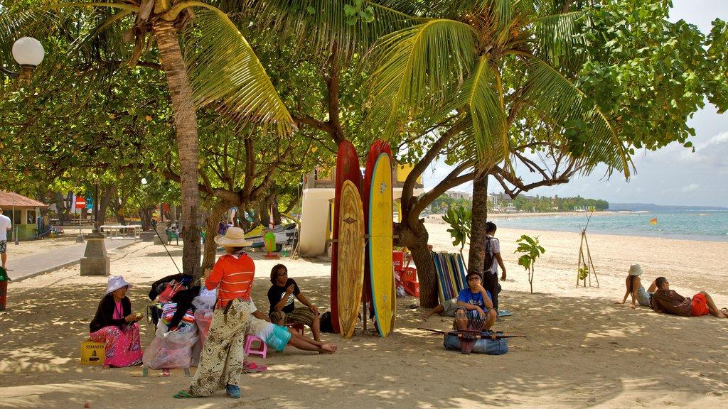 Kuta que incluye escenas tropicales y una playa de arena y también un pequeño grupo de personas