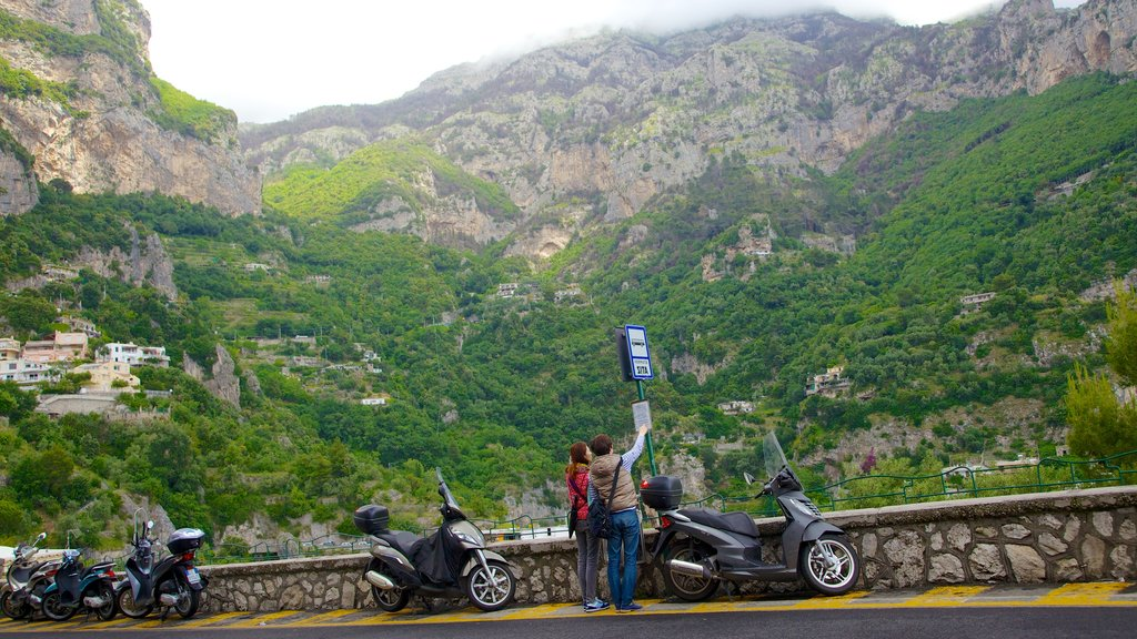 Positano showing mountains and motorbike riding as well as a couple