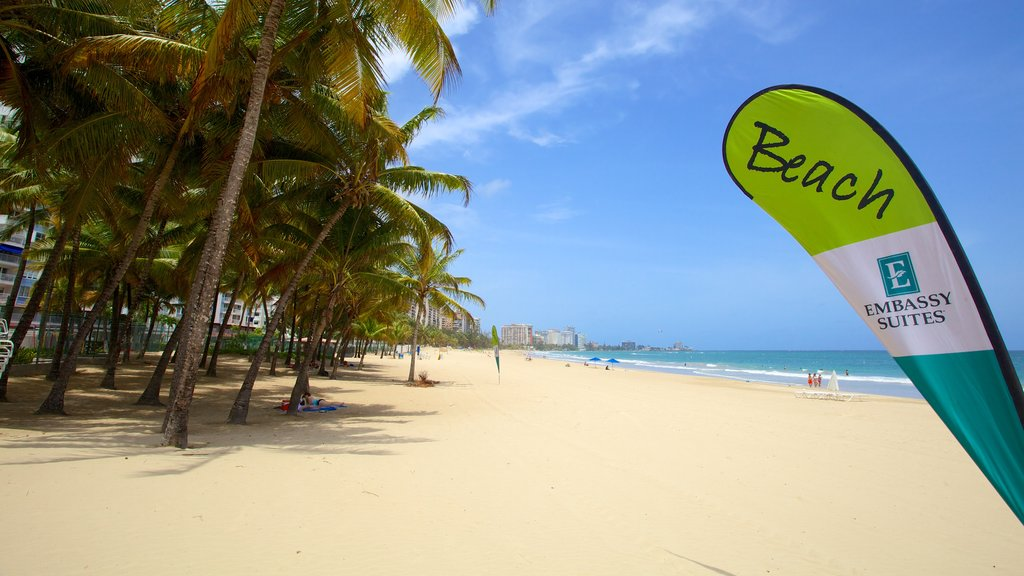 Isla Verde Beach which includes a sandy beach, tropical scenes and signage