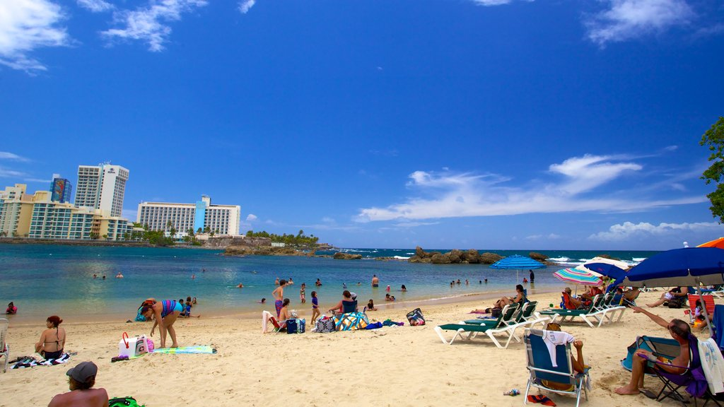 Condado Beach showing a sandy beach as well as a large group of people