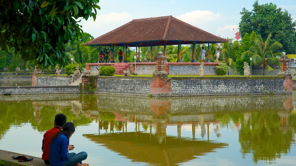 Mataram featuring a temple or place of worship and a pond as well as a couple