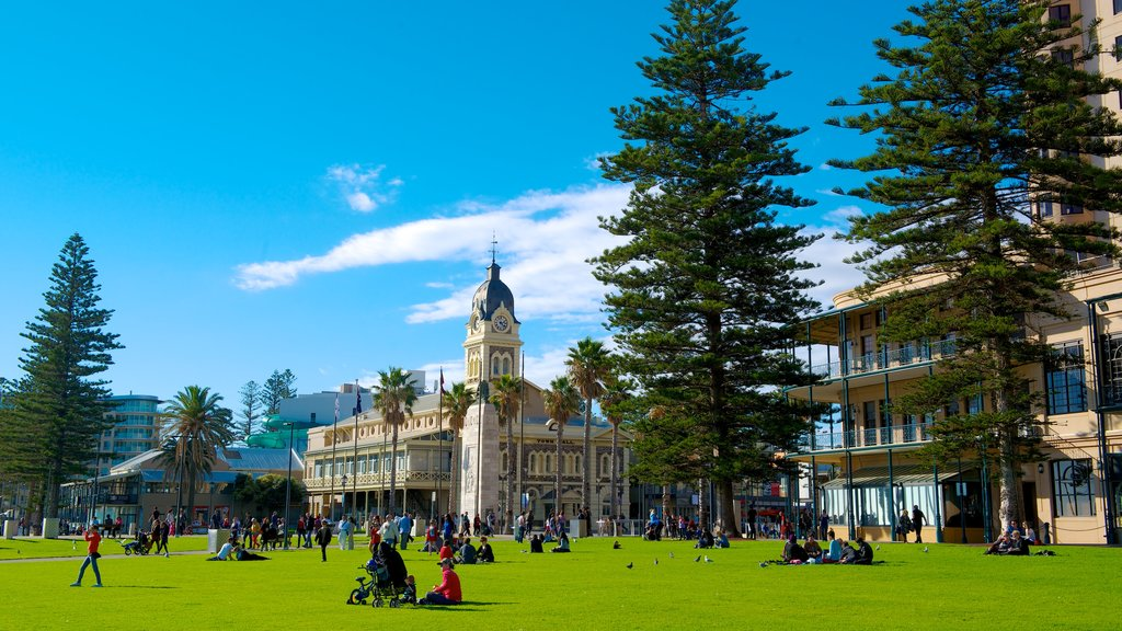Glenelg Beach showing a garden and a city as well as a large group of people