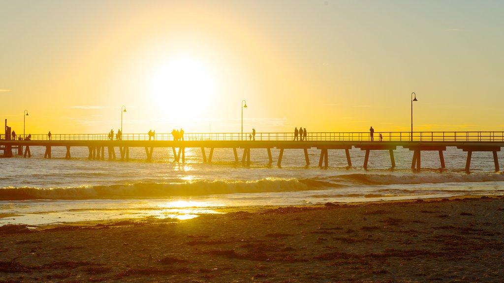 Glenelg Beach showing a sandy beach, a bridge and a sunset