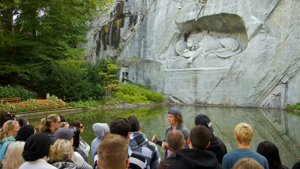 Lion Monument which includes a pond and a monument as well as a large group of people