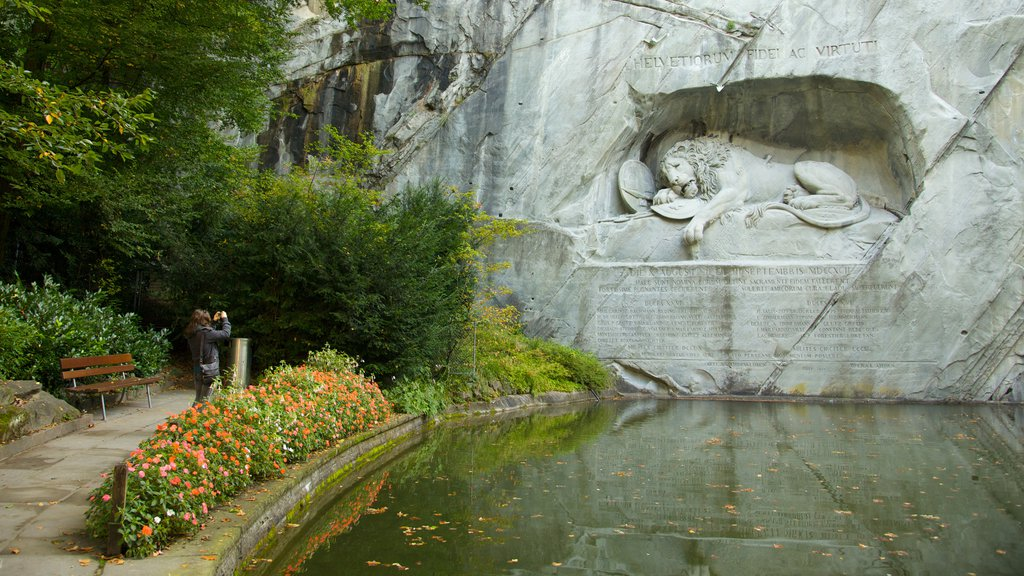 Lion Monument featuring a monument, a park and a pond
