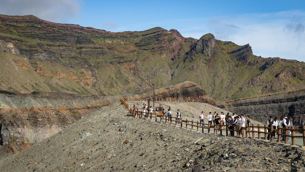 Mount Aso showing landscape views and mountains as well as a small group of people