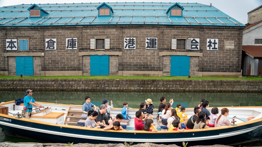 Otaru Canal which includes boating and a river or creek as well as a small group of people