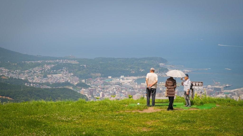 Monte Tengu que incluye vistas de paisajes y una ciudad costera y también un pequeño grupo de personas