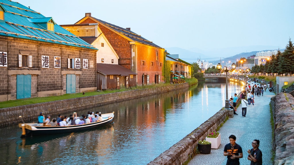 Otaru showing boating and a river or creek as well as a small group of people