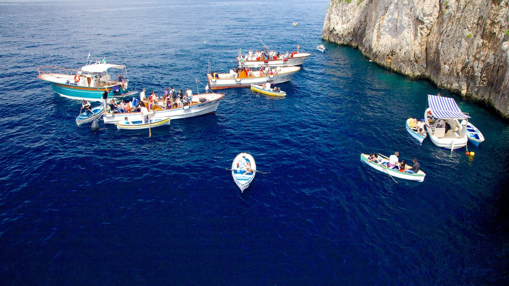 Blue Grotto showing rocky coastline and boating as well as a large group of people