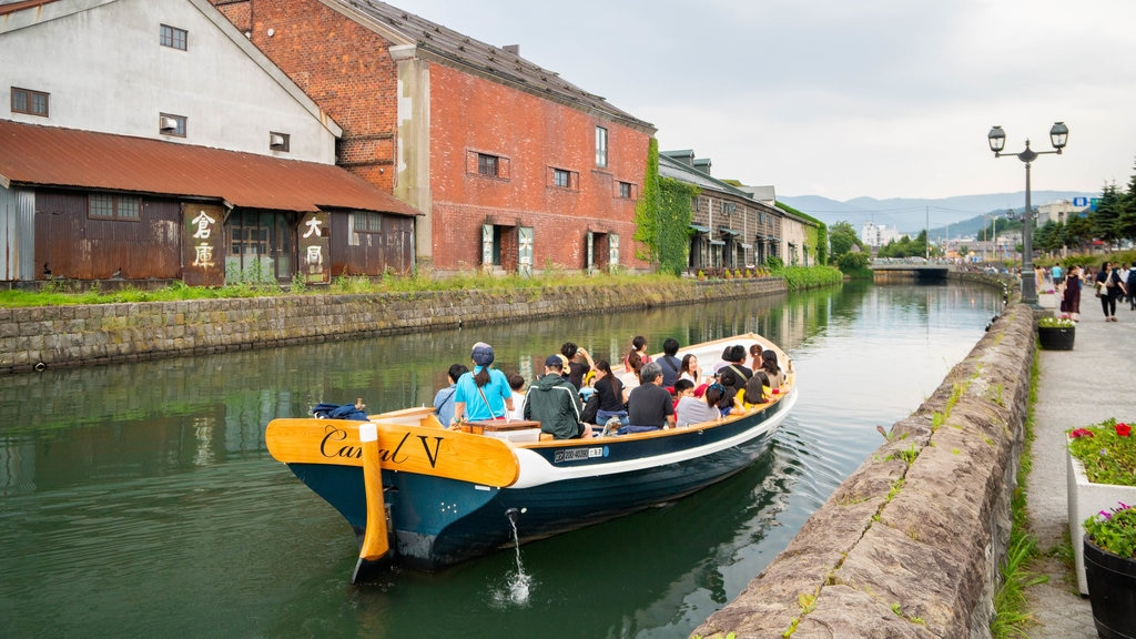 Otaru Canal showing a river or creek and boating as well as a small group of people