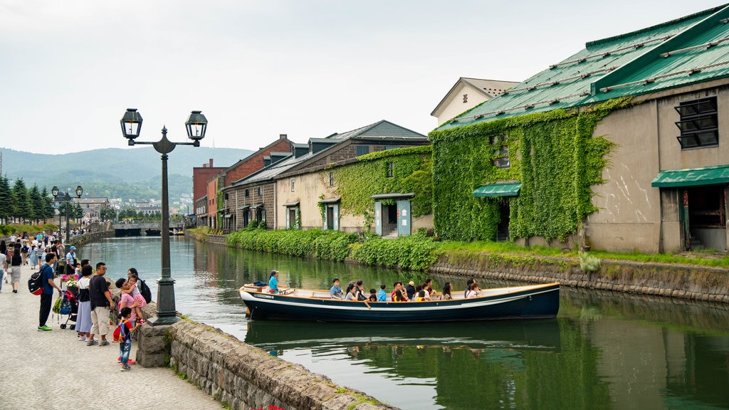 Otaru Canal featuring a river or creek and boating as well as a small group of people