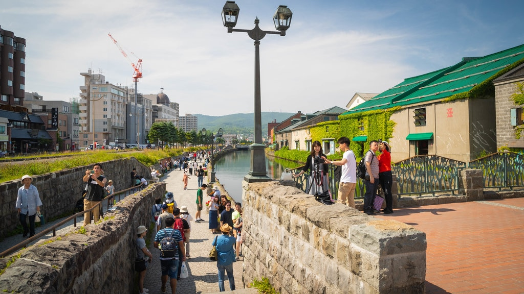 Otaru Canal which includes a river or creek and street scenes as well as a small group of people