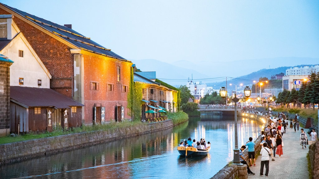 Otaru Canal showing boating and a river or creek as well as a small group of people