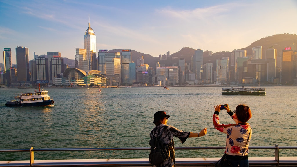 Tsim Sha Tsui Promenade which includes a bay or harbor, a sunset and a city