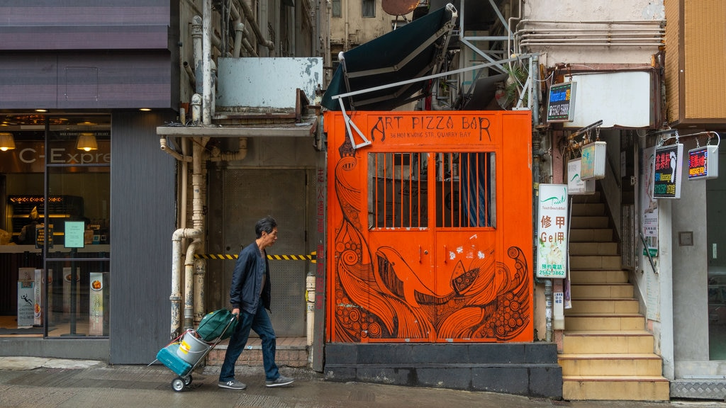 Tai Koo Shing featuring signage and street scenes as well as an individual male