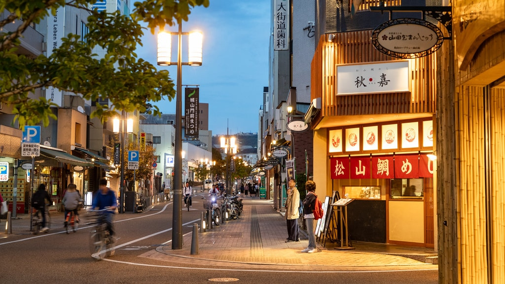 Matsuyama showing night scenes, street scenes and a city