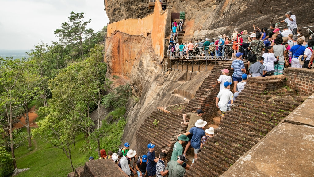 Sigiriya which includes a gorge or canyon and hiking or walking as well as a large group of people