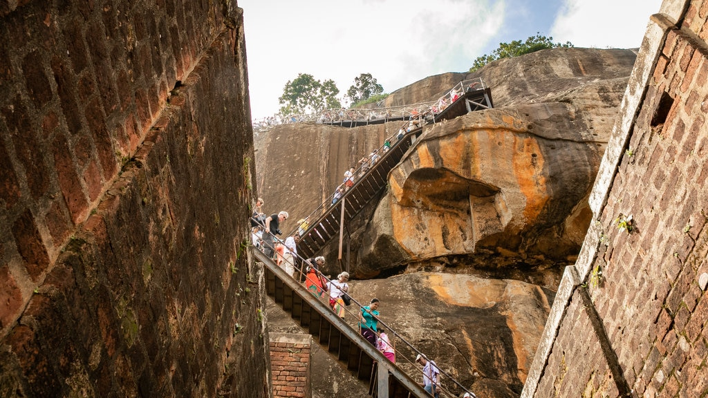 Sigiriya showing a gorge or canyon and hiking or walking as well as a small group of people
