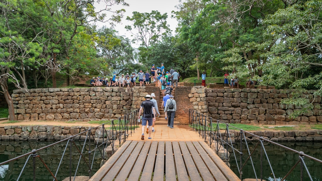 Sigiriya which includes a bridge and a park as well as a small group of people