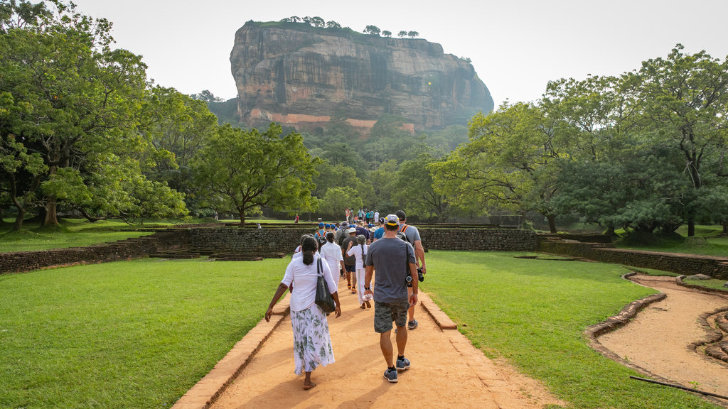 Sigiriya which includes a garden and mountains as well as a small group of people