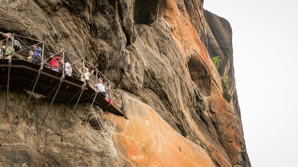 Sigiriya which includes a gorge or canyon and views as well as a small group of people