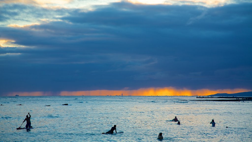Waikiki Beach showing surfing, a sunset and general coastal views