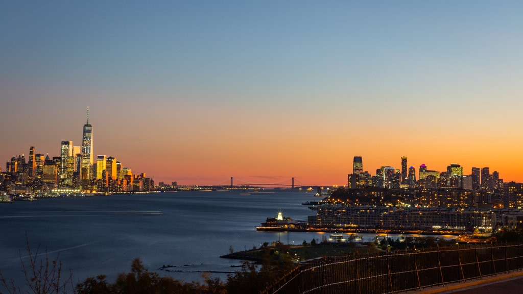 Lower Manhattan which includes a sunset, landscape views and a bay or harbor