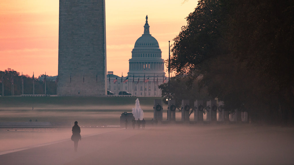United States Capitol featuring mist or fog, a sunset and an administrative buidling