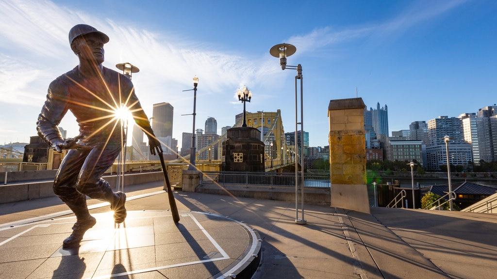 PNC Park showing a sunset, a bridge and a statue or sculpture