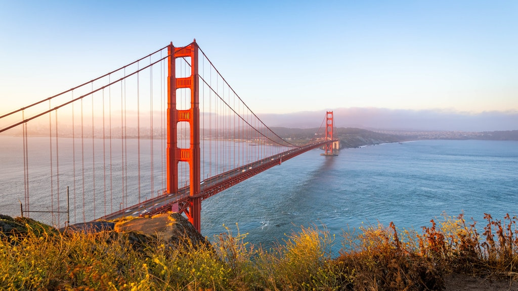 Golden Gate Bridge featuring landscape views, a river or creek and a sunset