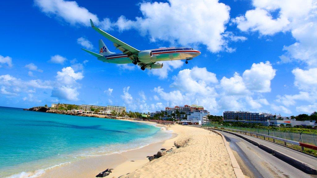 Maho Reef showing a sandy beach, aircraft and a coastal town