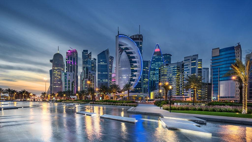 Doha Corniche showing a skyscraper, night scenes and a city
