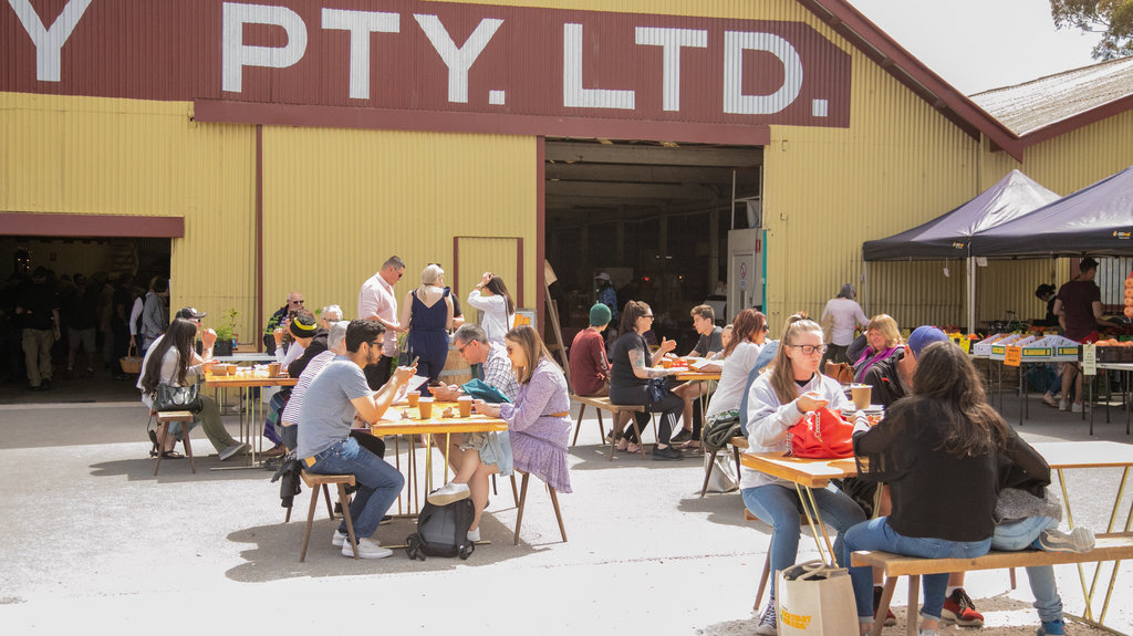Barossa Farmers Market showing signage and outdoor eating as well as a small group of people