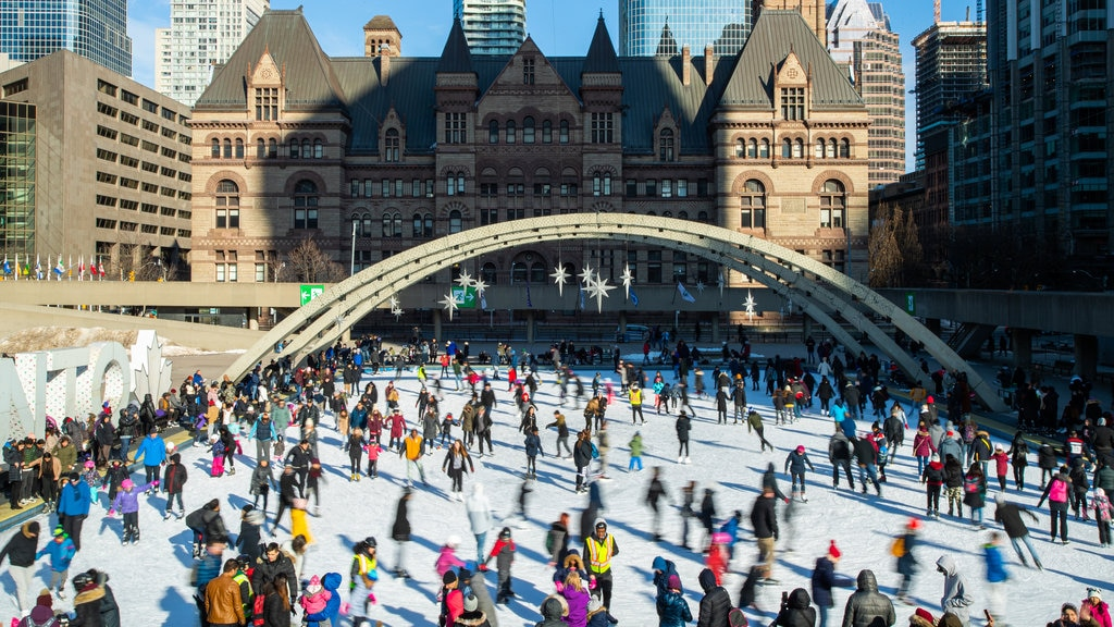 Nathan Phillips Square showing snow skiing and a city as well as a large group of people