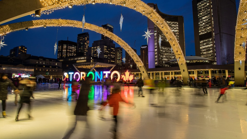 Nathan Phillips Square which includes snow skiing, a city and night scenes