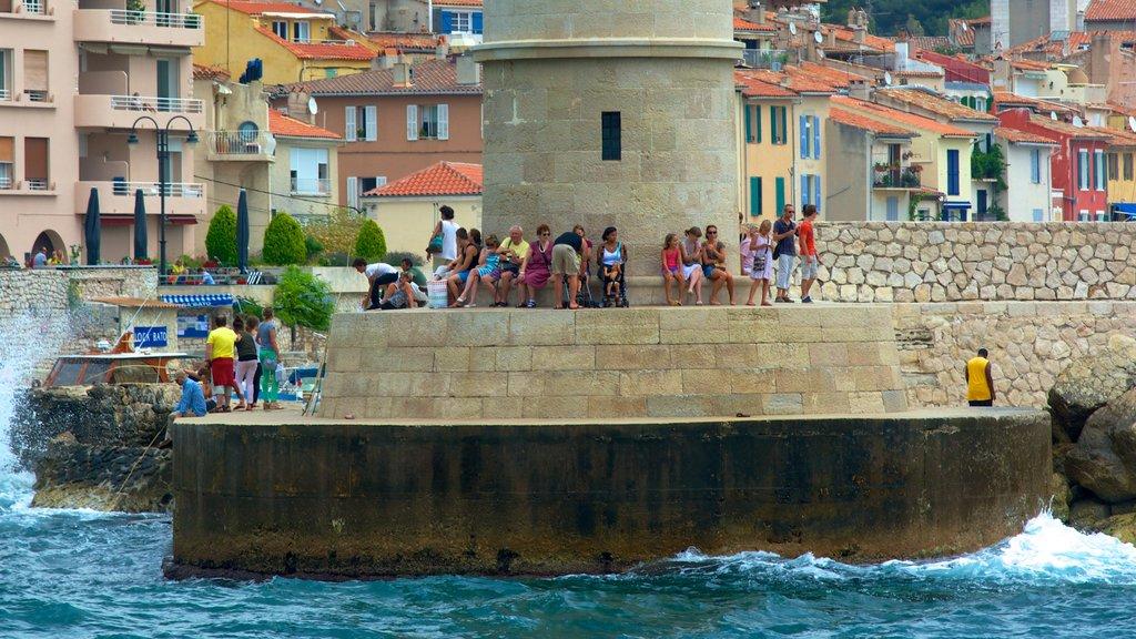 Cassis ofreciendo una ciudad costera y un faro y también un gran grupo de personas