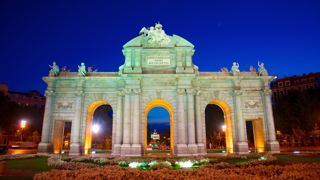 Puerta de Alcala which includes heritage architecture, flowers and night scenes