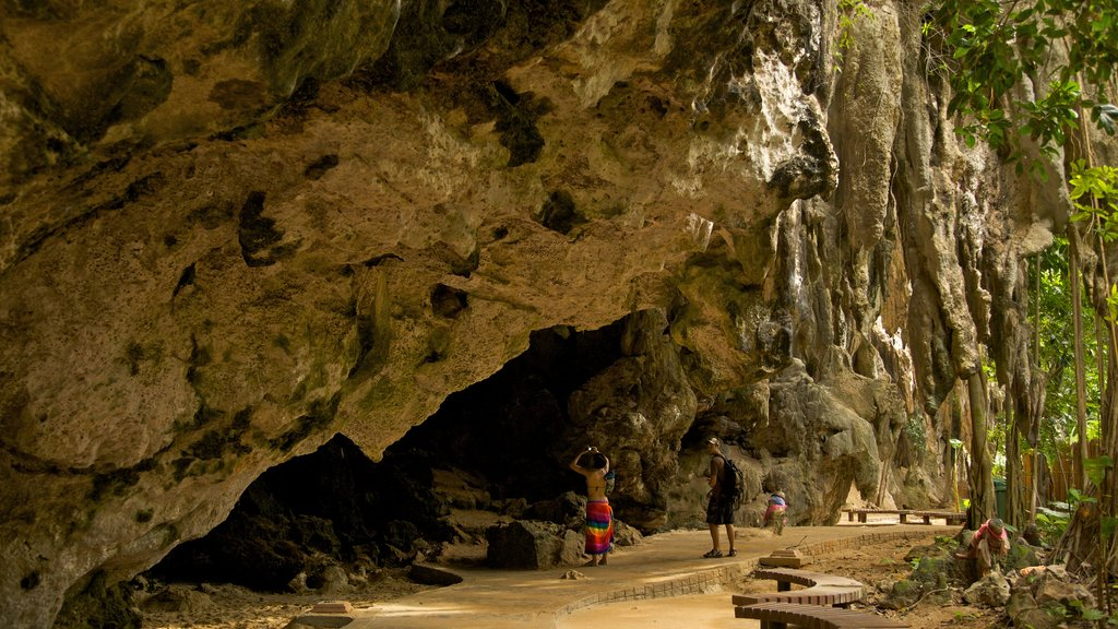 Krabi featuring caving and landscape views as well as a small group of people