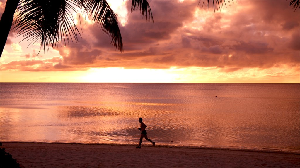 Tumon Beach which includes a sunset and a beach as well as an individual male