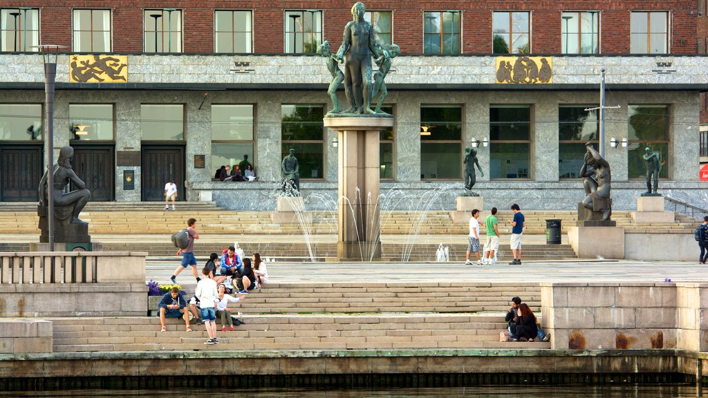 Aker Brygge which includes a statue or sculpture, a square or plaza and a fountain