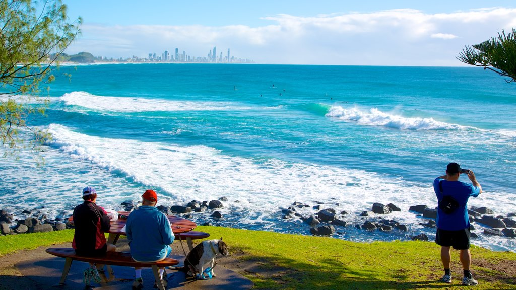 Burleigh Heads showing rugged coastline and surf as well as a small group of people