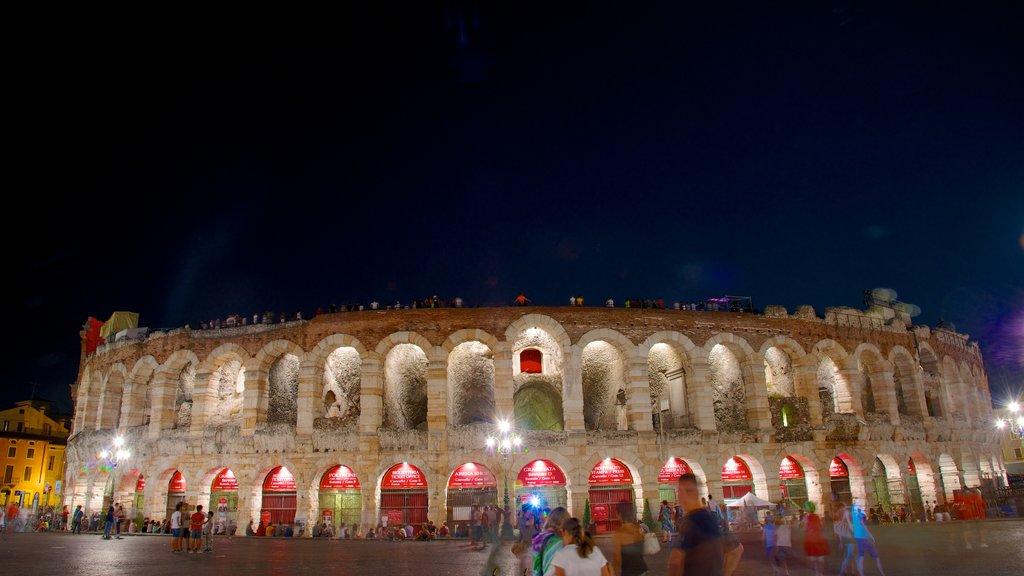 Arena di Verona showing night scenes, a city and building ruins