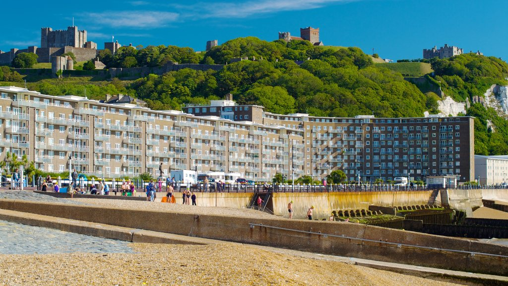 Dover Beach showing a beach and heritage architecture as well as a large group of people
