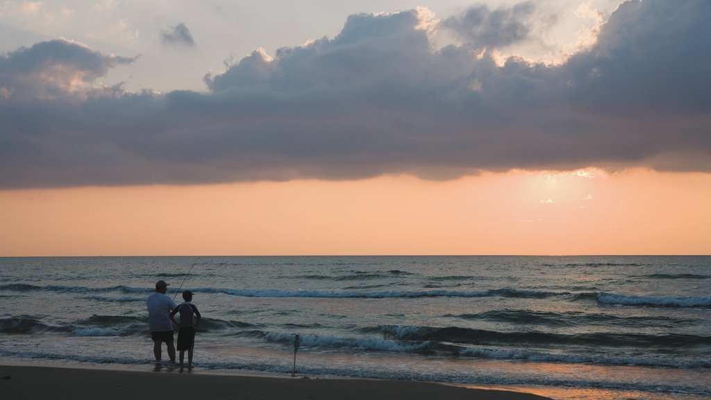 South Padre Island featuring a sandy beach, fishing and a sunset