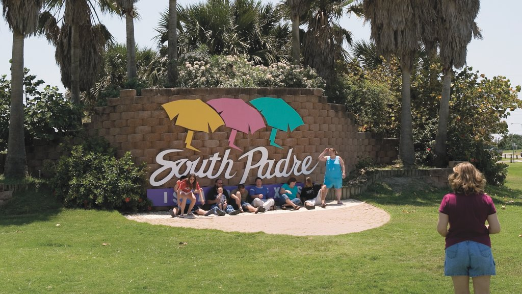 South Padre Island which includes signage and a garden as well as a small group of people