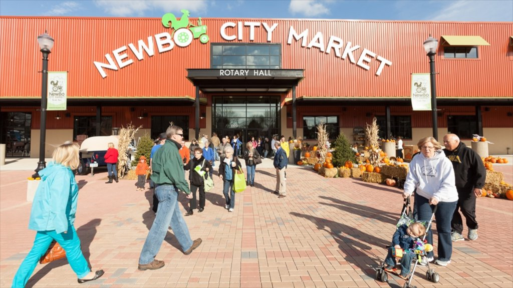 Cedar Rapids featuring signage and markets as well as a large group of people