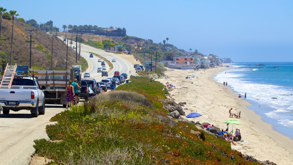 Malibu featuring a sandy beach and a coastal town as well as a large group of people