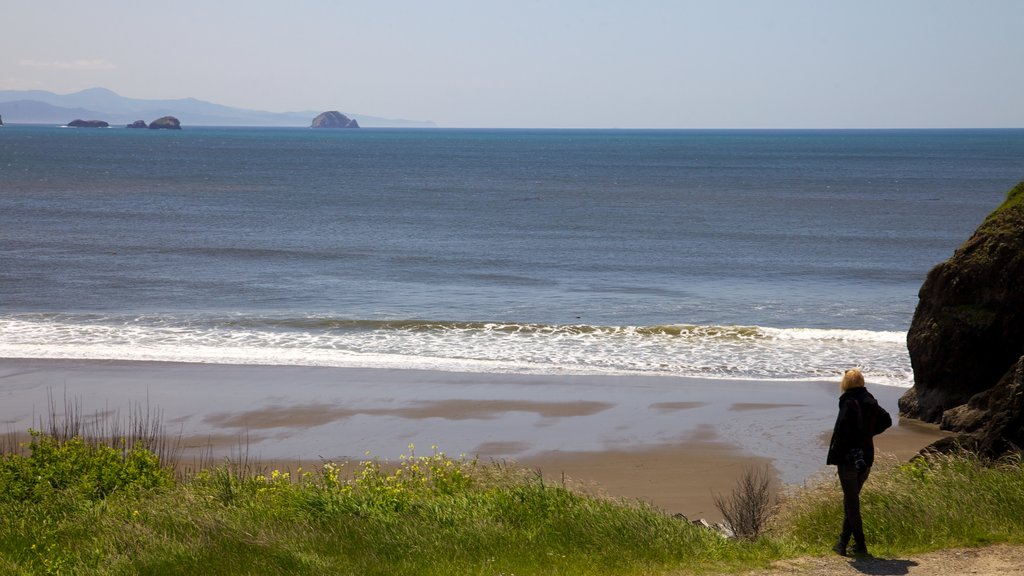 Port Orford featuring a sandy beach and landscape views as well as an individual femail